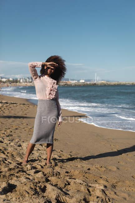 Jeune femme avec la coiffure afro restant sur la plage — Photo de stock