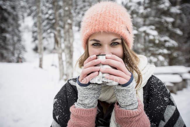 Портрет молодої жінки питної гарячого напою на відкритому повітрі взимку — стокове фото