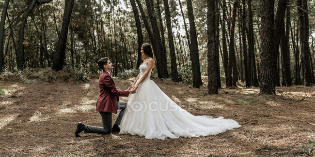 Man kneeling making a marriage proposal to happy bride in forest — Stock Photo
