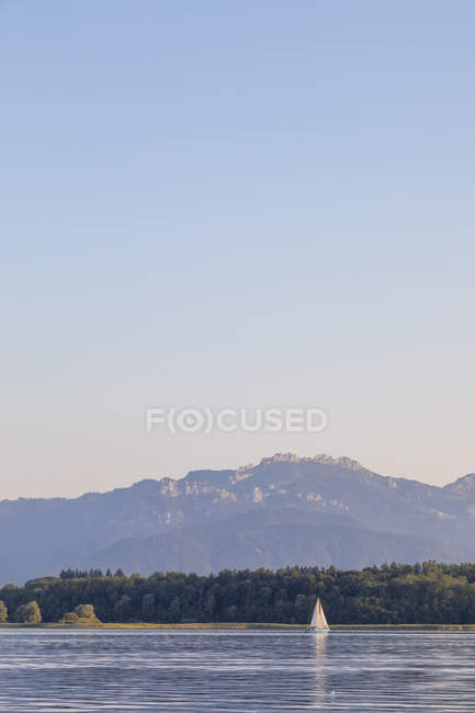 Germany, Bavaria, Chiemsee, sailing boat in the evening light — Stock Photo