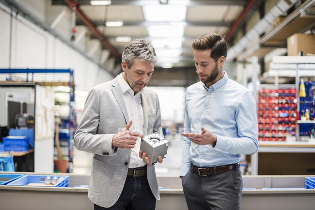 Businessmen during meeting with a product in production hall — Stock Photo