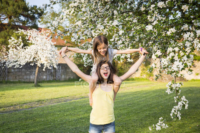 Girl carrying little sister on her shoulders in the garden — Stock Photo
