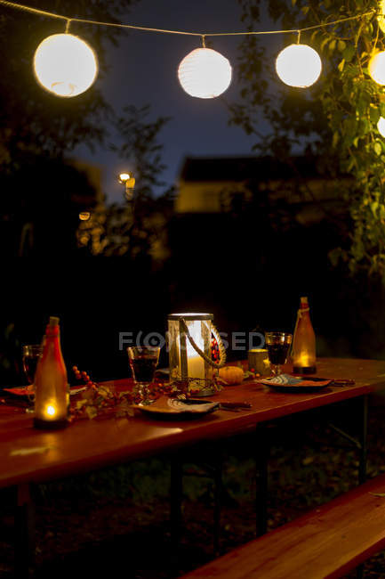 Laid table in garden at night — Stock Photo