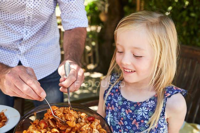 Padre che prepara pasta per la figlia al tavolo da giardino — Foto stock