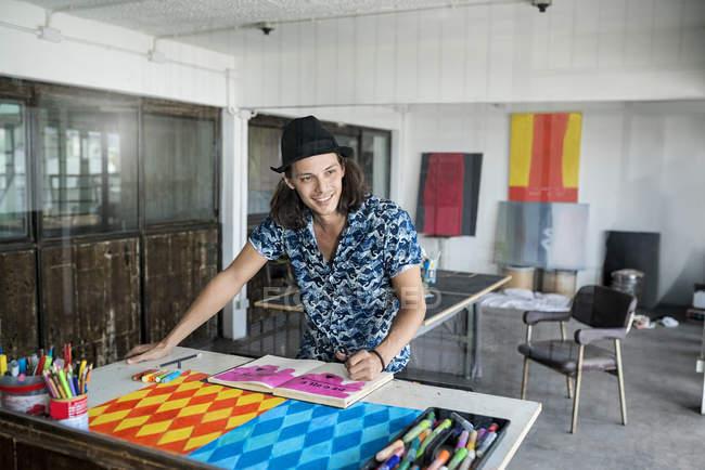 Lächelnder Künstler bei der Arbeit, Zeichnung in einem Notizbuch in seinem Loft-Atelier mit Gemälden und Kunstwerken im Hintergrund — Stockfoto