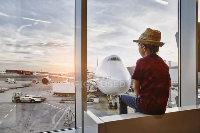 Menino usando chapéu de palha olhando através de janela para avião no avental — Fotografia de Stock