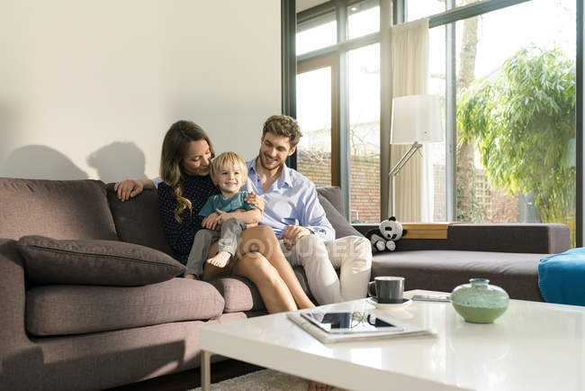 Smiling parents and son sitting on sofa at home — Stock Photo