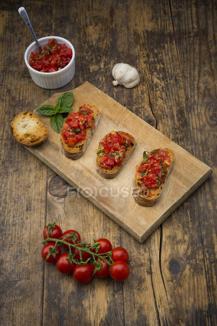 Bruschetta with tomatoes and basil on wooden board — Stock Photo