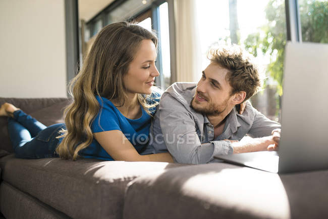 Smiling couple with laptop lying on sofa at home — Stock Photo