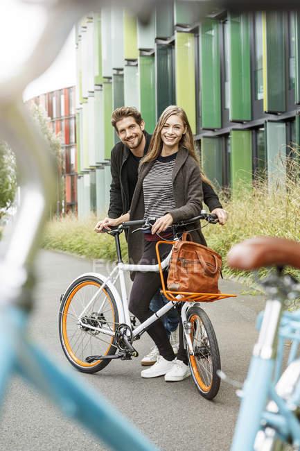 Portrait de couple souriant avec vélo sur une voie — Photo de stock