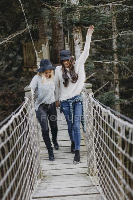 Две счастливые молодые женщины, идущие на подвеске вместе — стоковое фото