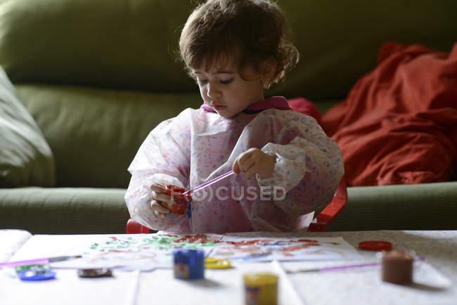 Маленька дівчинка малює вдома. — стокове фото
