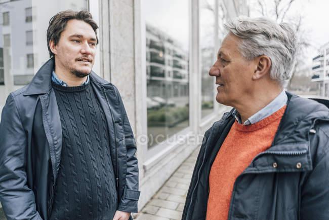 Jovem e idoso conversando na cidade — Fotografia de Stock