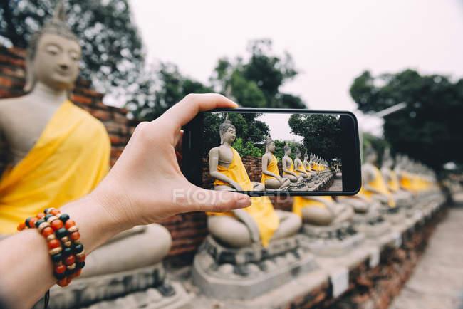 Thailand, Ayutthaya, Wat Yai Chai Mongkhon, taking a photo from Buddha with smartphone — Stock Photo