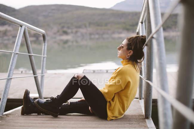 Giovane donna pensierosa rilassante sul molo — Foto stock