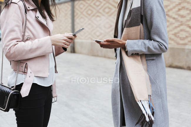 Close-up of women using cell phones in city — Stock Photo
