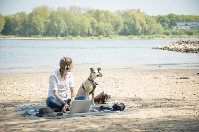 Жінка сидить на ковдрі біля річки з собакою в навушниках і за допомогою ноутбука. — стокове фото