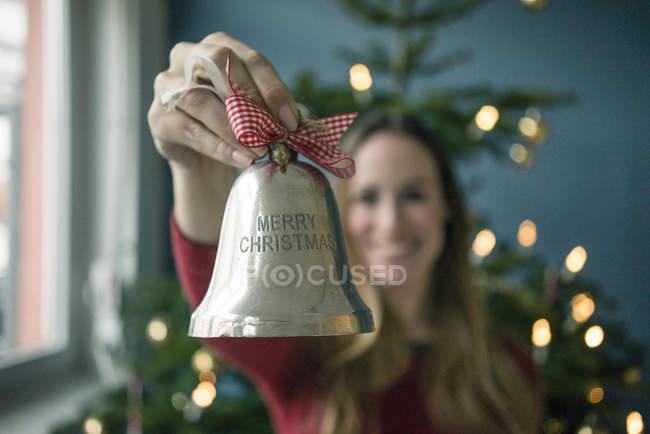 Рука женщины держит серебряный Рождественский колокол — стоковое фото
