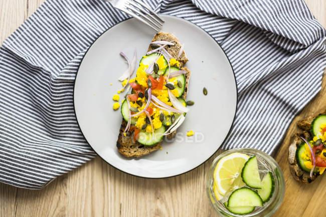 Вегетаріанський сніданок з хлібом, яйцями і шматочками огірків на тарілці — стокове фото