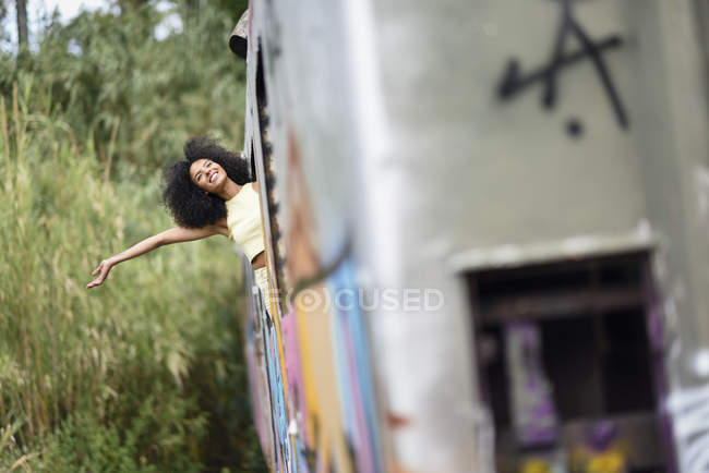Happy young woman leaning out of abandoned and destroyed old train — Stock Photo