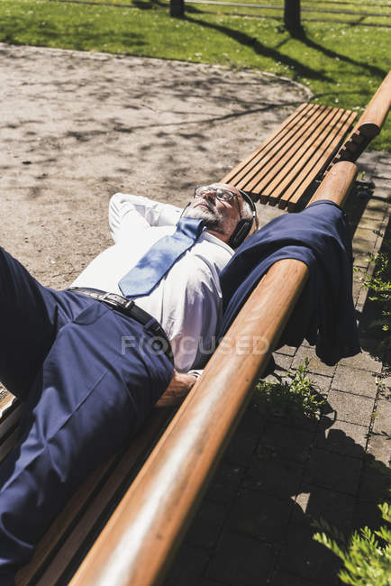 Mature businessman lying on a bench listening to music — Stock Photo