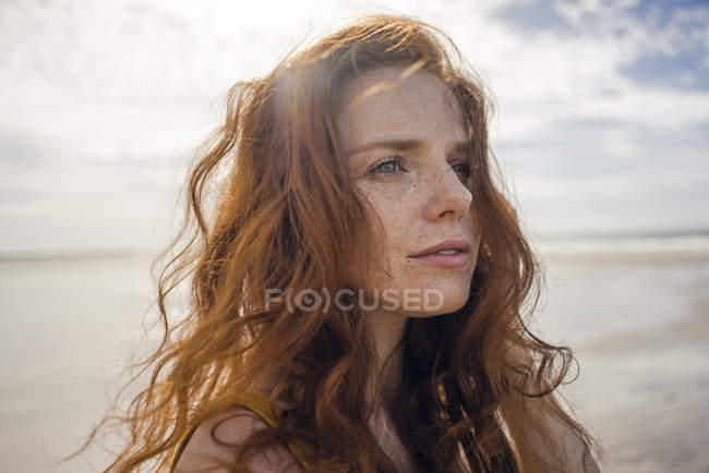 Portrait of a redheaded woman on the beach — стокове фото