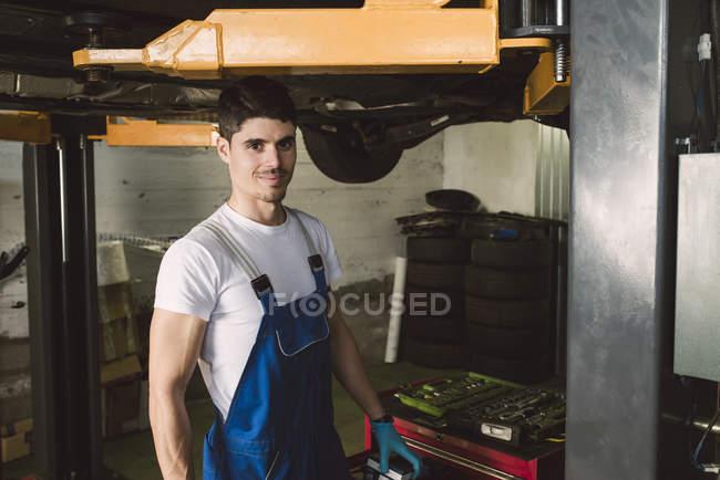 Портрет улыбающегося механика в мастерской — стоковое фото