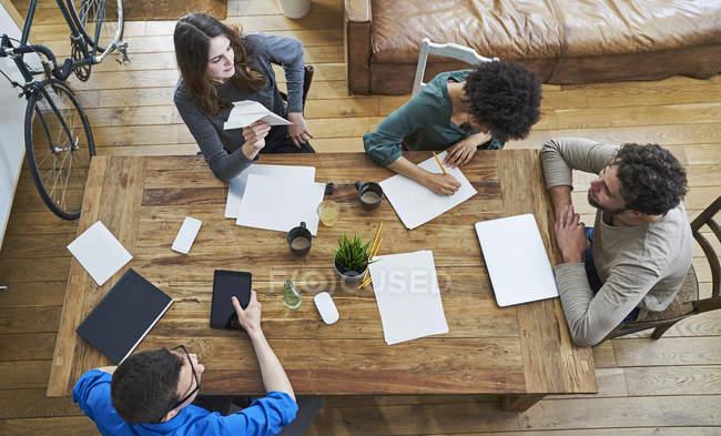 Повышенный вид сотрудников, работающих вместе за деревянным столом в офисе — стоковое фото