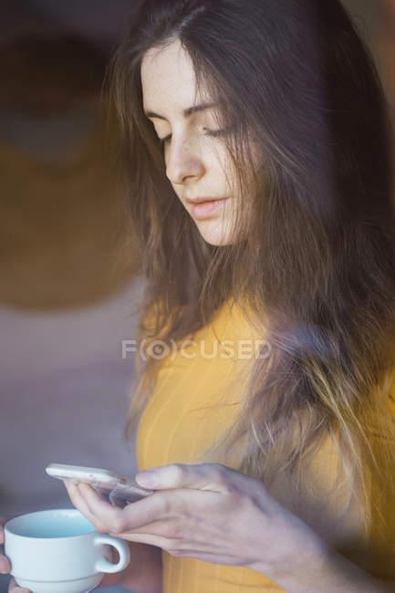 Portrait de jeune femme avec tasse à café regardant le téléphone cellulaire — Photo de stock