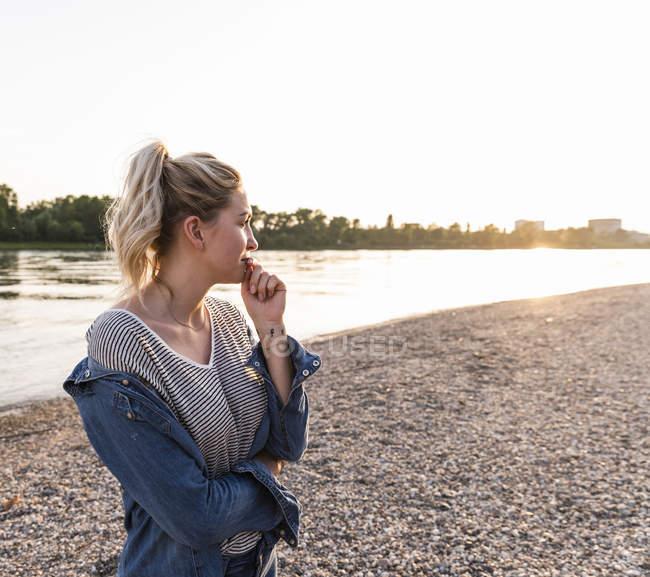 Jeune femme blonde qui attend au bord de la rivière le soir — Photo de stock