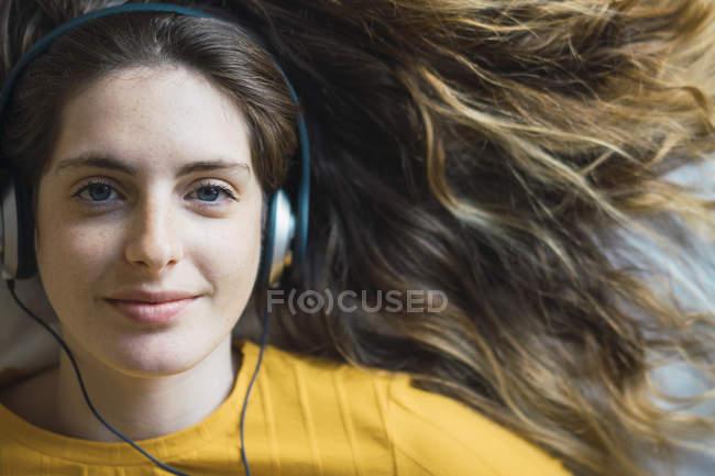 Ritratto di giovane donna sorridente con cuffie sdraiata sul letto — Foto stock
