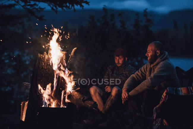 Canada British Columbia Two Men Sitting At Camp Fire At Boya