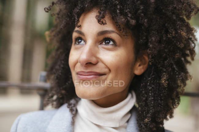 Портрет улыбающейся женщины смешанной расы, смотрящей вверх — стоковое фото