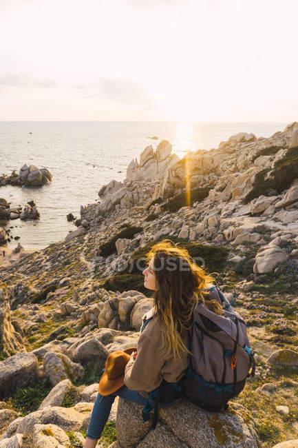 Italia, Cerdeña, mujer en un viaje de senderismo sentado en la roca en la costa - foto de stock