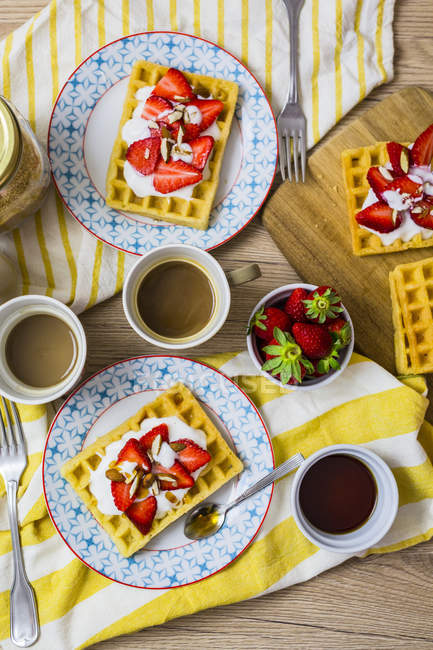 Two plates of waffles garnished with strawberries, Greek yogurt and almonds on breakfast table — Stock Photo