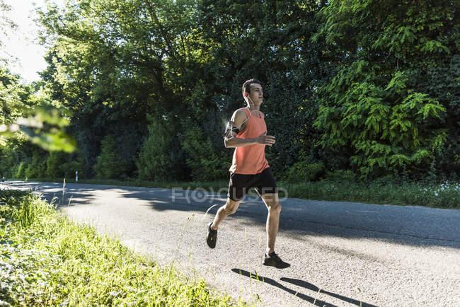 Молодой человек бежит в парке — стоковое фото