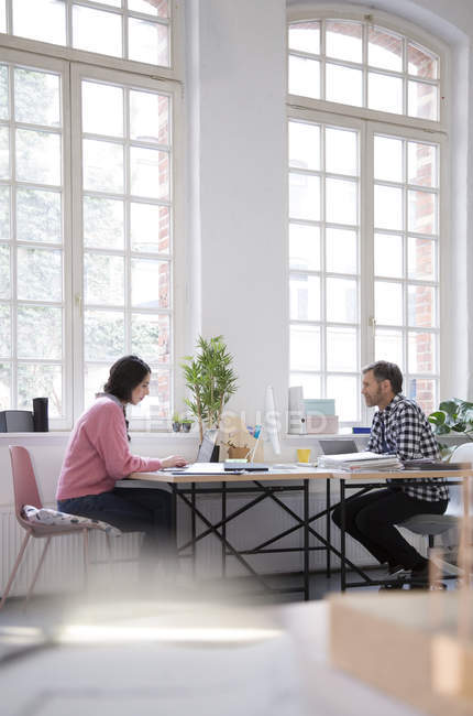 Colleagues working at desk in a loft office — Stock Photo