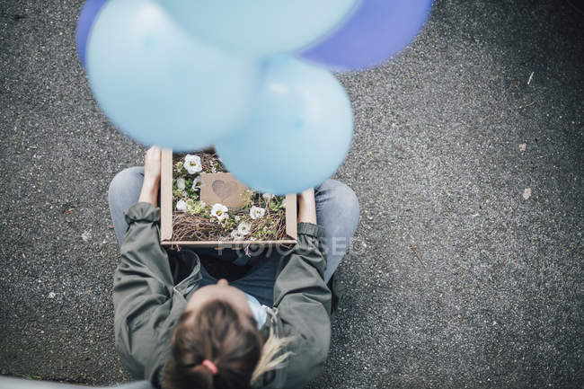 Woman with present in cardboard box and blue balloons sitting on the ground — Stock Photo