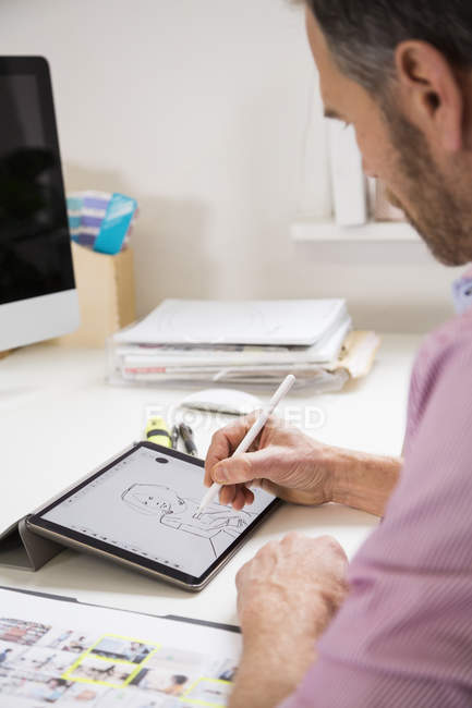Man working at desk in office drawing female figure on tablet — Stock Photo