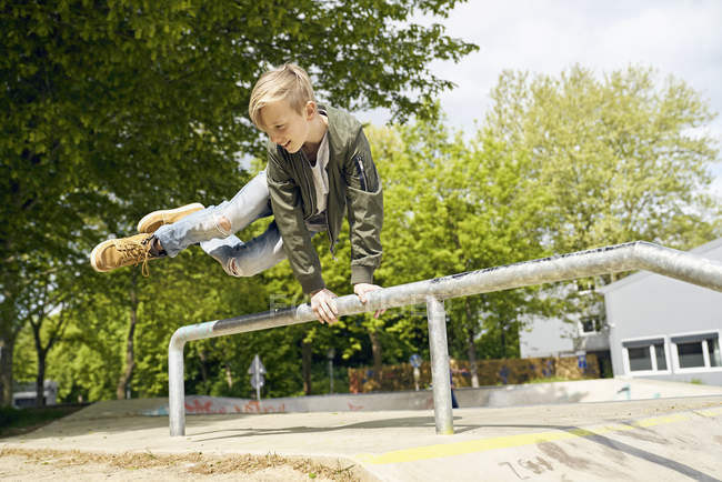 Boy jumping over railing in skatepark — Stock Photo