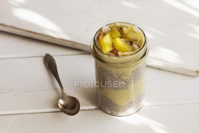 Vidro do pudim de Chia com o smoothie da manga decorado com flocos do quivi e do coco — Fotografia de Stock