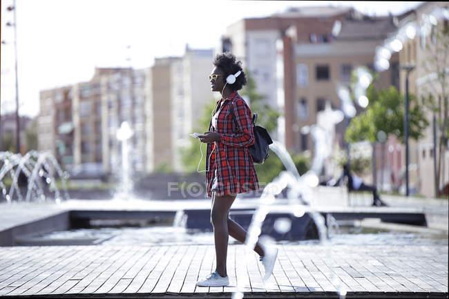 Молодая женщина с рюкзаком, смартфоном и наушниками гуляет по городу — стоковое фото