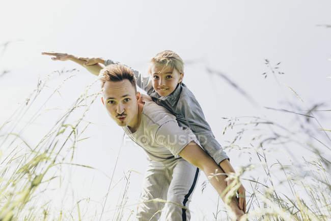 Junge und Mann auf einem Feld vortäuschen zu fliegen — Stockfoto