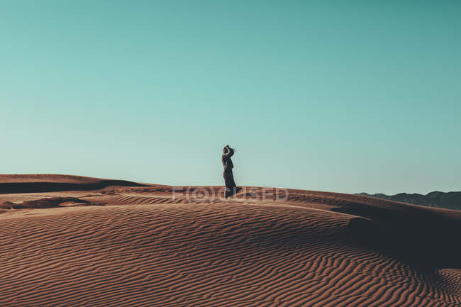 Young woman with windswept hair standing in desert landscape — Stock Photo
