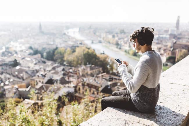 Italia, Verona, turista con smartphone y auriculares - foto de stock