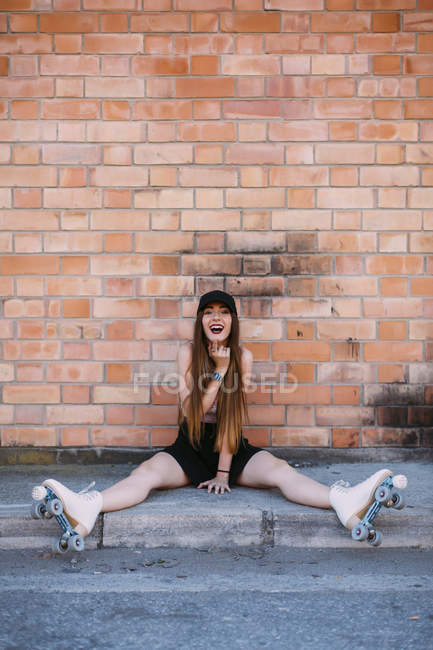 Portrait of laughing young woman  with roller skates sitting on sidewalk — Stock Photo