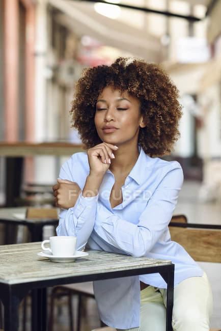 Розслаблена жінка з афро зачіска сидить у відкритому кафе — стокове фото