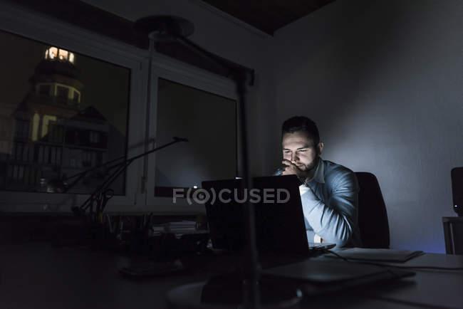 Homme d'affaires travaillant sur ordinateur portable dans le bureau la nuit — Photo de stock