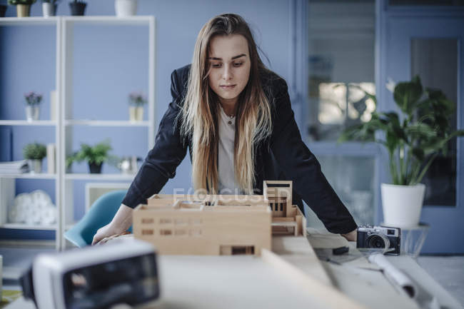 Architect woman looking at architectural model in office — Stock Photo