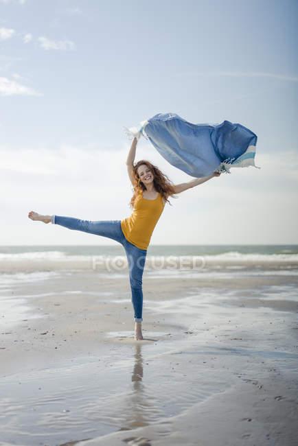 Donna felice divertirsi in spiaggia, ballare e asciugamano ondeggiante — Foto stock